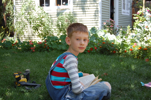 Emmett reading in the cool backyard shade.